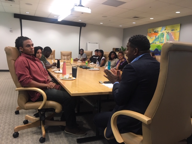 Calvin Butler talks with students around the table