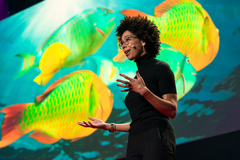Dr. Ayana Elizabeth Johnson gives a talk with image of fish behind her