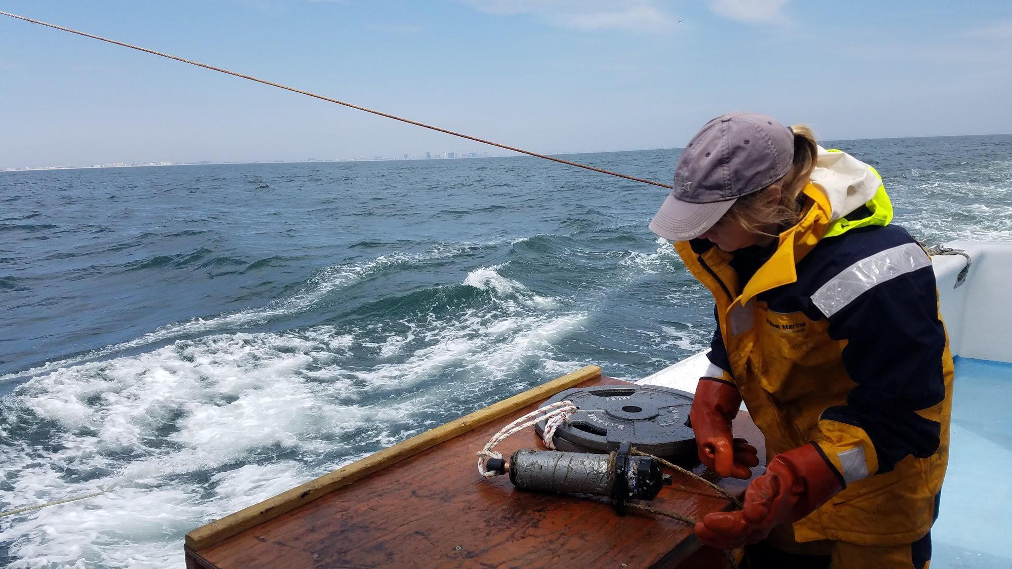 Ellie Rothermel configures acoustic reciever off coast of Ocean City, Maryland.