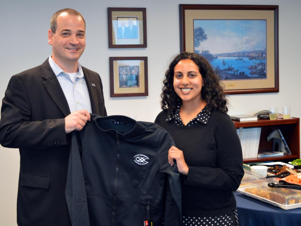 Saddef Haq receives her REEF jacket from Nicholas Hammond.