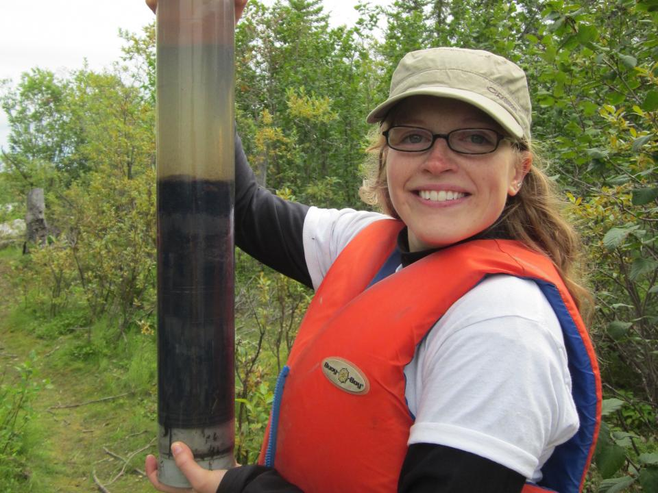 Grad student Hadley McIntosh holds up a soil sample in the field.
