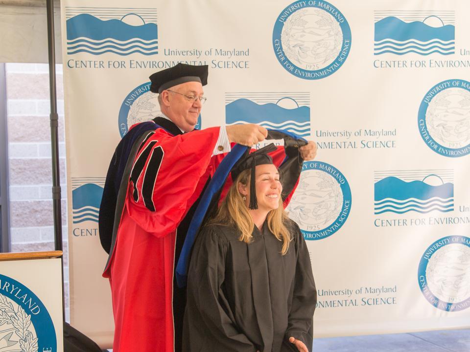 Tom Miller puts a hood on new graduate Danielle Zaveta