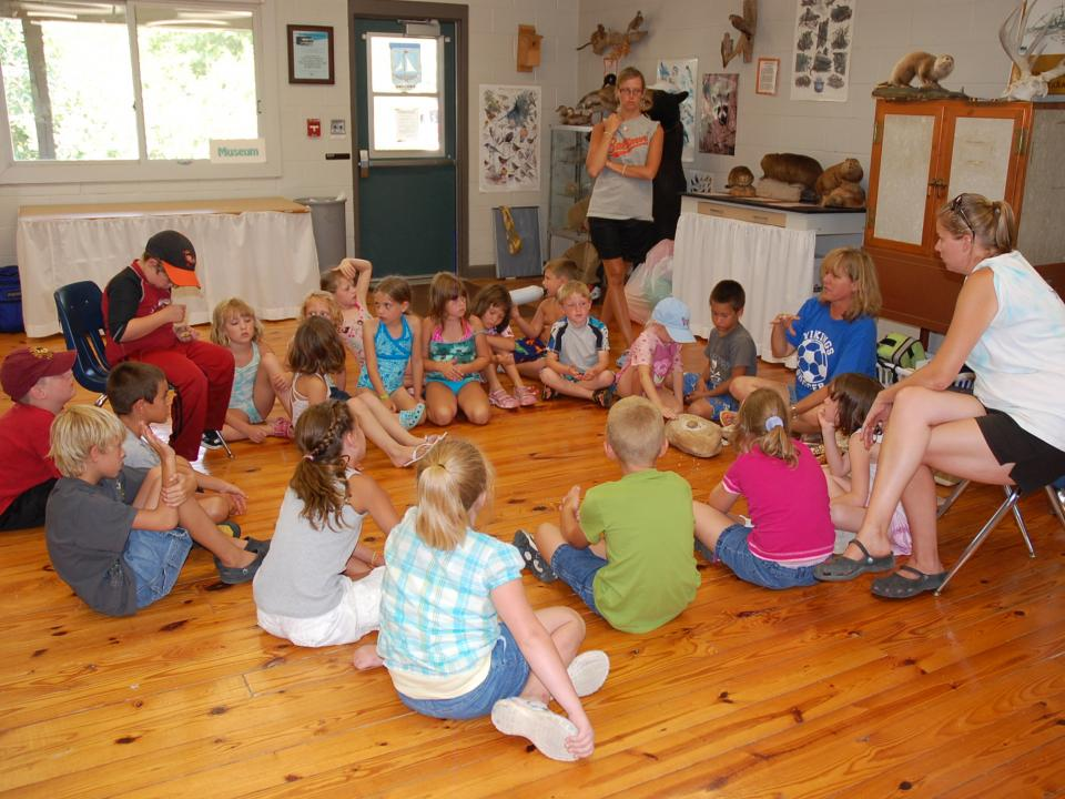 Group of students sitting in a circle listening to a lesson in the Outdoor Education Center