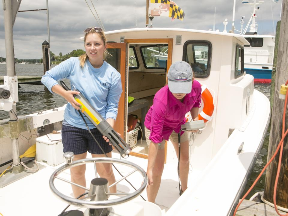 Two students ready on a boat get equipment ready to make water quality measurements