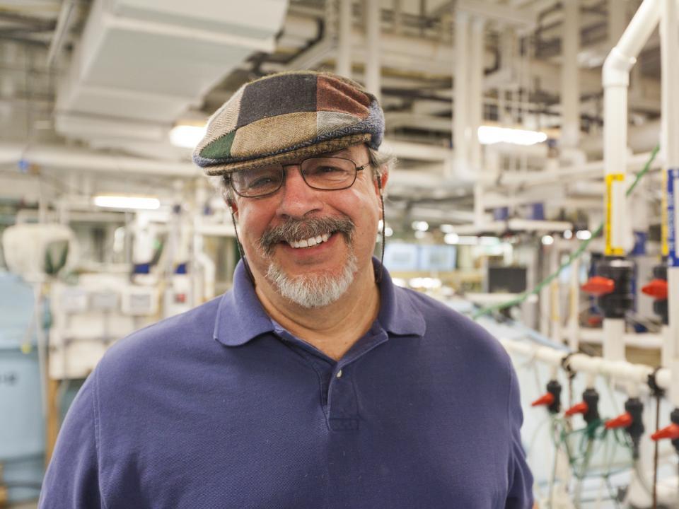 Scientist Al Place poses inside his lab's aquaculture facility.