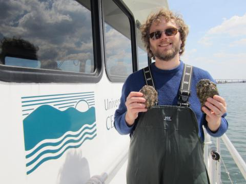 Mike Wilberg stands on deck of Rachel Carson research vessel holding oysters