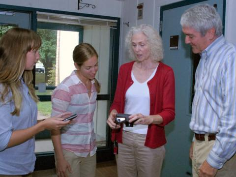 Kathy and Mike Quattrone of Chesapeake Seasons, Inc. based in Bozman, Maryland explain a special underwater camera to Horn Point Laboratory graduate students Melanie Jackson and Cassie Gurbitz.