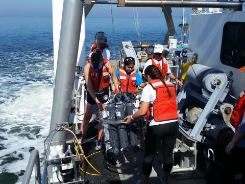 Students in the biological oceanography class lift a CTD rosette to lower it into the water.