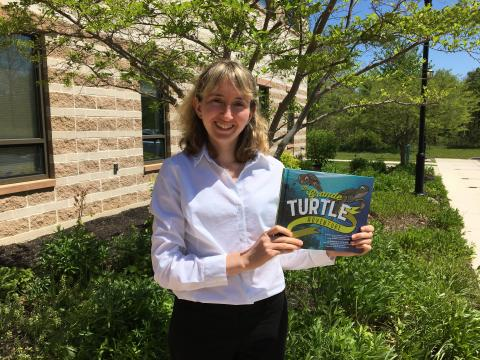 Dr. Helen Bailey poses with the children's book she wrote, The Grande Turtle Adventure.