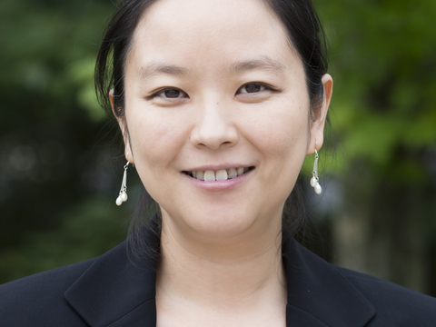 Head shot of Xin Zhang with green leaves in background.