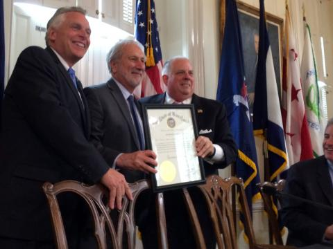 Gov. Larry Hogan presents UMCES President Don Boesch with a Maryland governor's citation while Virginia Gov. Terry McAuliffe (far left) looks on.