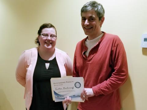 Tsetso Bachvaroff poses with the certificate he received from Kaila Noland and the other graduate students.
