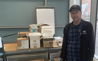 IMET Director Russell Hill stands next to boxes of personal protective gear for the COVID-19 response.
