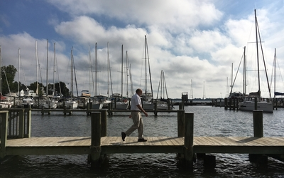 A man walks along a pier in a Annapolis with sailboats behind him.
