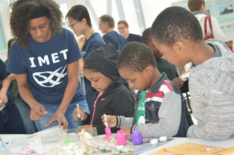 Amanda Lawrence works with children as they paint crabs at the IMET Open House.