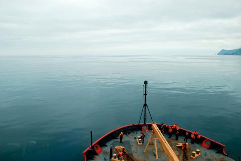 USCGC Healy peeks into frame as it cruises through Arctic waters.