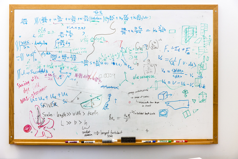 Whiteboard with science formulas written across it.