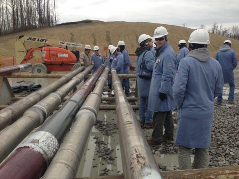 workers gather around pipes to allow oil drilling.