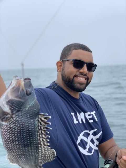 Ben Frey, alumnus of the IMET summer program holding a fish