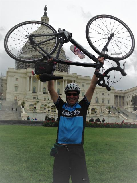 Eric Davidson hoists up his bike in front of Washington DC's Capitol after completing a Climate Ride.