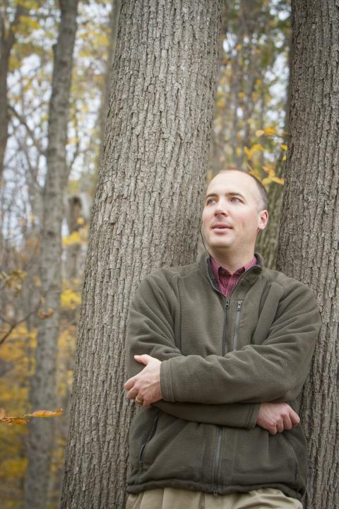 A portrait of Dave Nelson standing in a forest. Dave Nelson will be using stable forms of carbon, 12 and 13, to determine how much heat and drought stressed red spruce trees in different locations at different points in time. Photo by Cheryl Nemazie