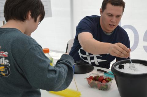 IMET graduate student Ryan McDonald shows a visitor to the Open House how to extract DNA from a strawberry.