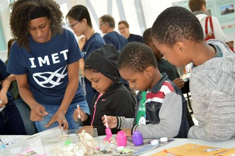 Graduate student Amanda Lawrence shows young visitors how to pipette at IMET's inaugural Open House in 2017.
