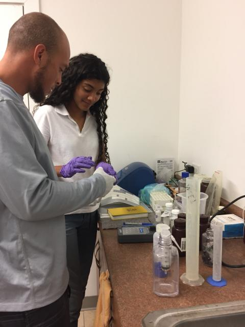 Two students examine samples in a lab.