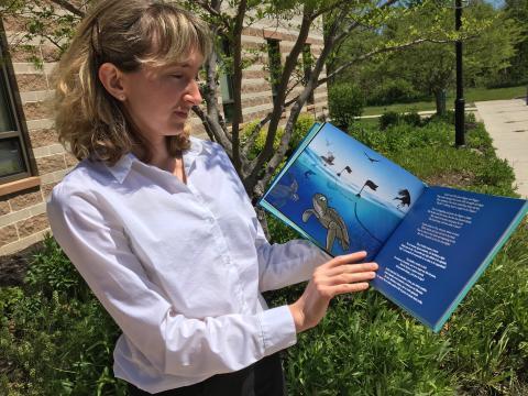 Helen Bailey holds up her children's book, the Grande Turtle Adventure.