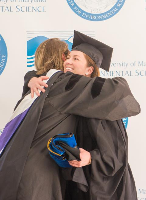 Lora Harris hugs her student, Jessica Foley, who earned her master's degree.