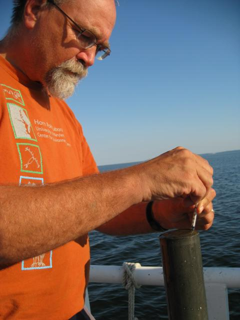 Jeff Cornwell works with a core of sediment pulled from Chesapeake Bay.