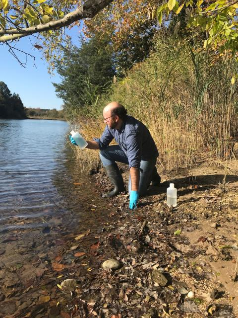Louis Plough a collects a water sample to test for DNA evidence of river herring in the lab.