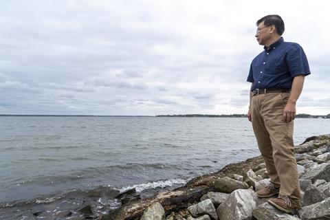 Coastal scientist Ming Li stands along the shoreline of the Choptank River