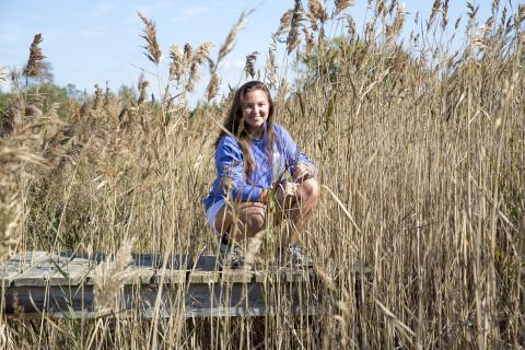 Graduate student Hannah Morrissette pictured in a research marsh