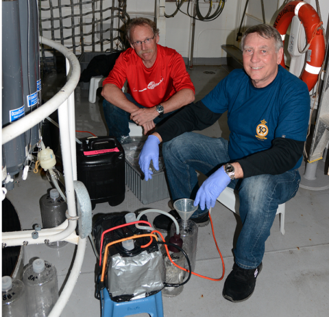 Raleigh Hood and Michael Landry (Scripps Institution of Oceanography) filtering water from the CTD in preparation for experiments conducted on the aft deck of RV Investigator.