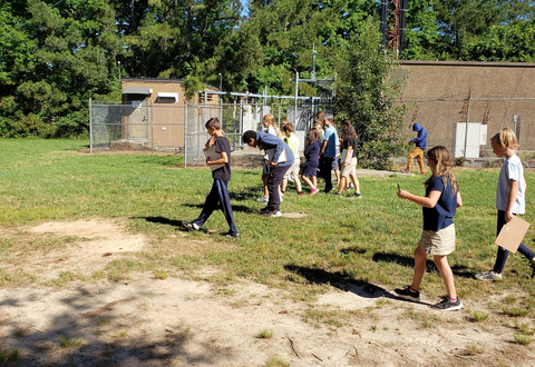 Students survey plastic waste on their school grounds.