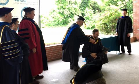 Christopher Paver kneels so his advisor, Research Professor Lou Codispoti, can drape him in his graduation hood during the 2018 commencement.
