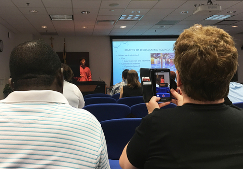 Proud parents filming their son giving presentation at conclusion of IMET summer internship program