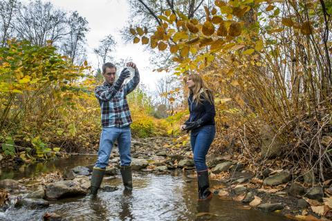 two people testing water in a stream