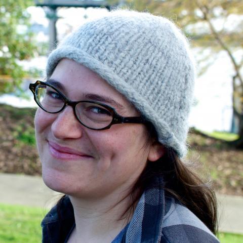 Headshot of smiling Dr. Clara Fuchsman wearing grey knit hat and eyeglasses