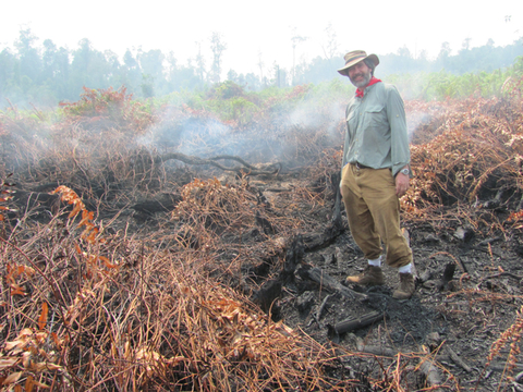 Mark Cochrane stands in a peat field that's smoldering from a wildfire.