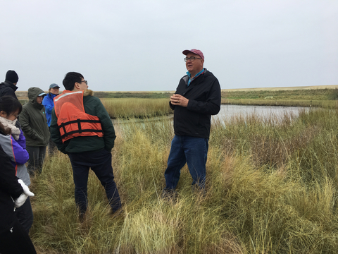 Jeff Cornwell Speaking to students on Poplar Island among marsh grass