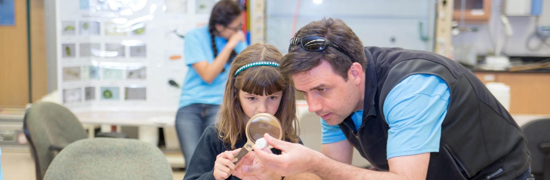 Matt Fitzpatrick helps a little girl examine a sample through a magnifying glass