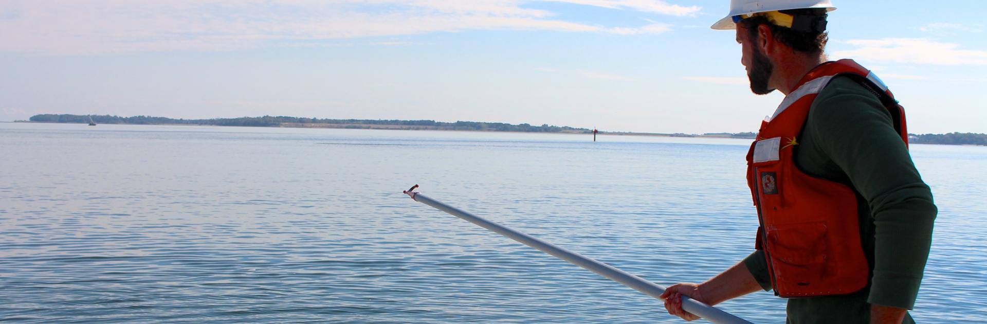 person standing in the water with a pole