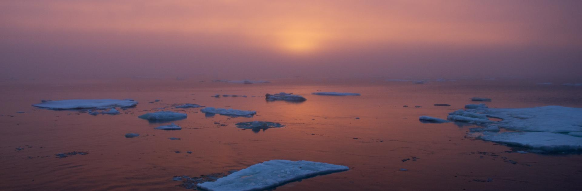 The sun sets over ice-dotted Arctic waters. Photo by Johnny Sullivan, US Coast Guard