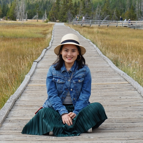 Mingli sits on a boardwalk among grasses