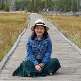 Mingli sits on a boardwalk among grasses
